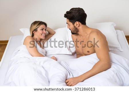 attractive couple laying in bed and talking stock photo 371286013 shutterstock. Black Bedroom Furniture Sets. Home Design Ideas