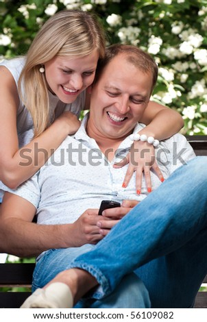 Attractive couple looks at the screen of a cell phone