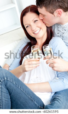 Attractive couple lying on the sofa and drinking champagne at home