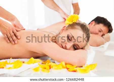 Attractive couple lying side by side in a spa enjoying the luxury of a deep tissue back massage together