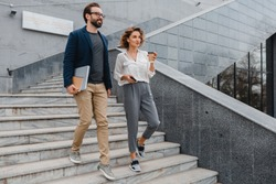 attractive couple of man and woman going on stairs in urban city center in smart casual business style, talking, working together, smiling, stylish freelance people, holding laptop? discussing