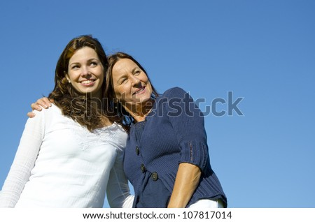 Attractive couple of mother and daughter hugging on a sunny  day outside, with clear blue sky as background and copy space.