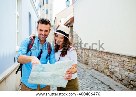 Attractive couple on vacation, sightseeing old town with map #400406476