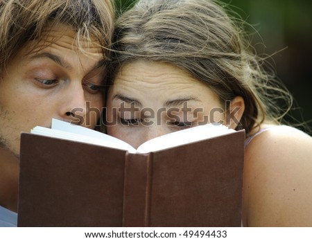Attractive couple read together in the park #49494433