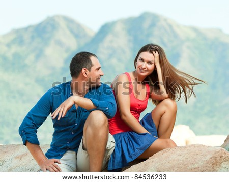 Attractive couple sitting on the cliff. Mountain on background