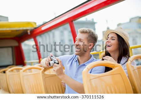 Attractive couple with camera in a tour bus