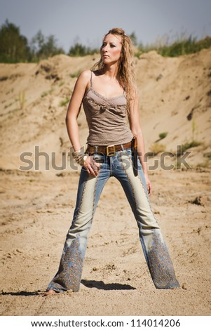 Attractive cowgirl in jeans on a sandy background