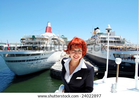 Attractive crew member on the top deck of a cruise ship going through the port