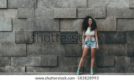 Attractive curly brunette hipster smiling girl in teal jeans shorts in front of street stoned patterned wall background on bright day with copy space for advertising message or your logo #583828993