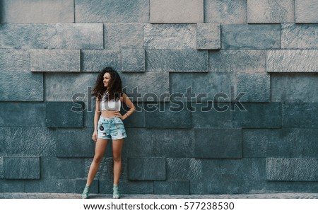 Attractive curly brunette hipster smiling girl in teal jeans shorts looking aside while standing in front of street stoned patterned wall background with copy space for your message, logo or promotion #577238530