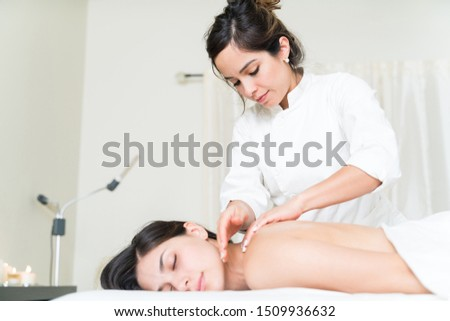 Attractive customer sleeping while beautiful masseuse giving neck massage at healthcare center