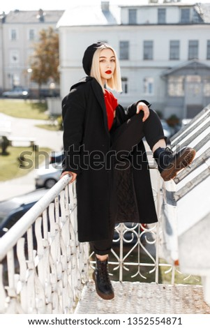 Attractive cute woman blonde with red lips in a vintage beret in a black coat in a stylish red shirt in pants in leather shoes is resting outdoors in the city. Fashion girl fashion model. Retro style.