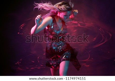 Photo of Attractive dancing blonde in the club, neon light, motion effects. Black background, long exposure