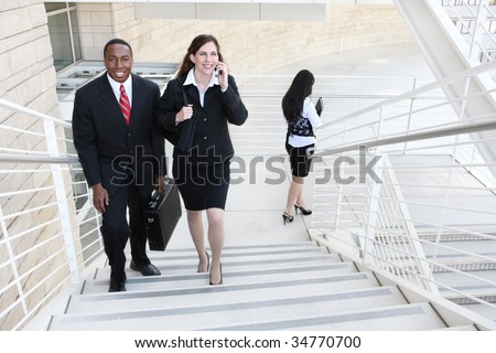 Attractive diverse business man and woman team walking up stairs to work