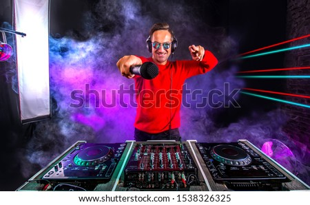 Attractive Dj with microphone  playing on the turntable at night club. Club, nightlife.
