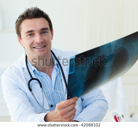 Attractive doctor examining an x-ray and smiling at the camera