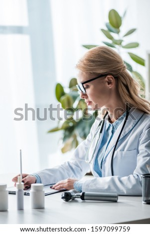 attractive doctor in glasses writing diagnosis in clinic