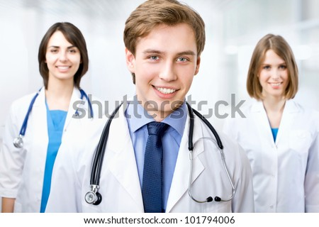 Attractive doctor standing with his colleagues in a hospital
