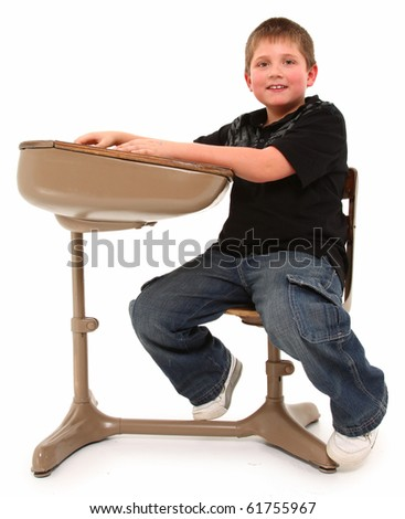 Attractive eight year old boy in school desk over white background.