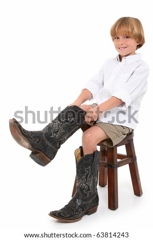 Attractive eight year old boy putting on dad's boots over white background. - stock photo