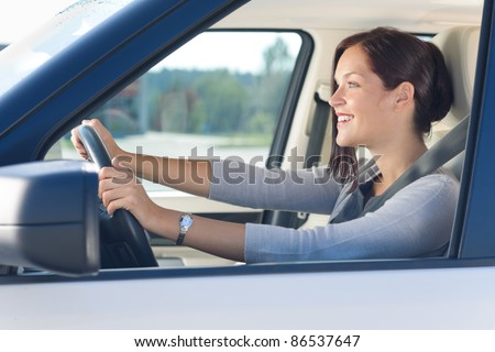 Attractive elegant businesswoman driving luxury new car concentrating