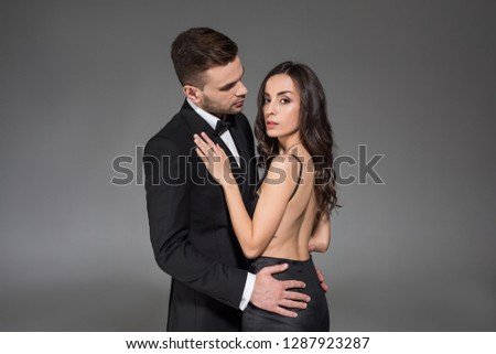 attractive elegant couple in black clothes hugging isolated on grey #1287923287