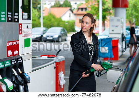 attractive elegant woman in black dress refuel car on gas station