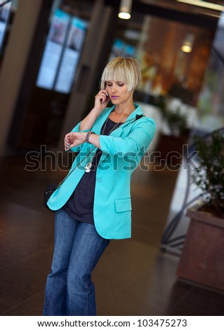 attractive elegant woman waiting and looking at her wrist watch in the street