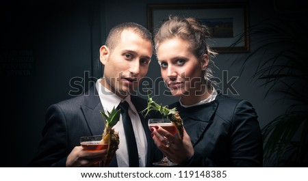 Attractive elegant young couple drinking a cocktail.