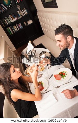 Attractive elegant young couple drinking to each others celebrating at the restaurant.