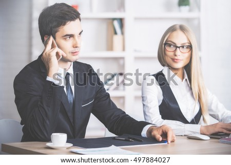 Attractive european businessman and woman working and talking on mobile phone at workplace - Shutterstock ID 497884027