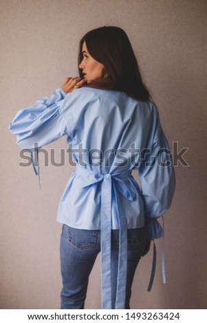 Attractive european female showing her sensuality and feminine features, sensual, playfully and dreaming. Feeling confident and carefree. Girl wear blue blouses. Rare view. Girl is turn around.