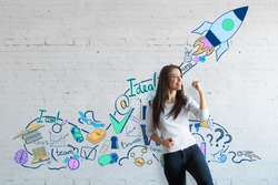 Attractive european woman celebrating success on brick wall background with creative drawn space ship. Successful young entrepreneur