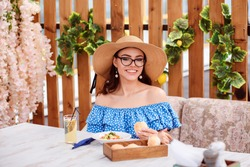 Attractive European woman is having lunch in the outdoor cafe veranda. Summertime. Beautiful woman is wearing sunglasses, wide-brim hat and blue dress with frills.