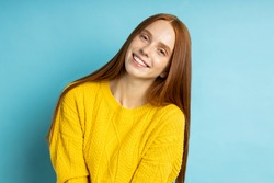 Attractive excited happy woman with red long hair, freckles, no make up smiling cheerfully showing her perfect white teeth, wearing yellow sweter posing on blue background.