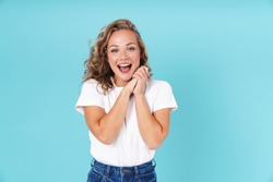 Attractive excited young girl wearing casual clothing standing isolated over blue background, looking at camera