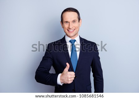 Attractive, executive, corporate, cheerful, positive politician, economist, financier in formal wear with tie, making thumb up, standing over gray background