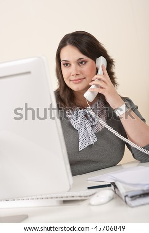 Attractive executive woman on phone at office watching computer screen