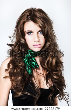Attractive fashion model with curly hair looking into camera