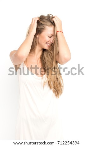 Stock Photo attractive fashion model with long blond hair posing in studio in white dress, simple make up, sexy body, smiling, laughing and grimacing, isolated on white background