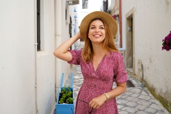 Attractive fashion woman walking in narrow alley of typical old town of Italy