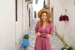 Attractive fashion woman walking looking down in narrow alley of typical old town of Italy