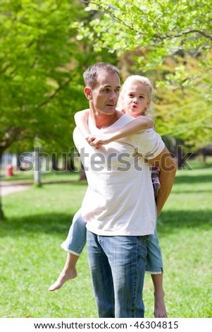 Attractive father giving his daughter piggy-back ride in a park