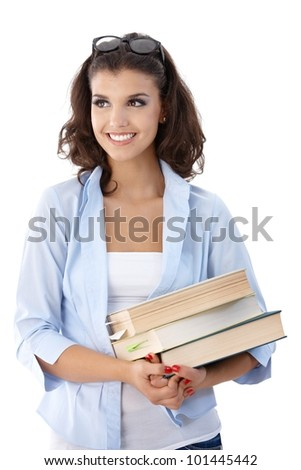 Attractive female college student holding books, looking away.