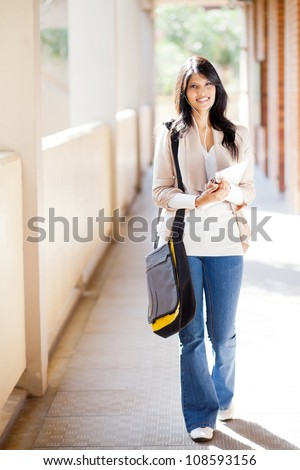 attractive female college student walking down school corridor