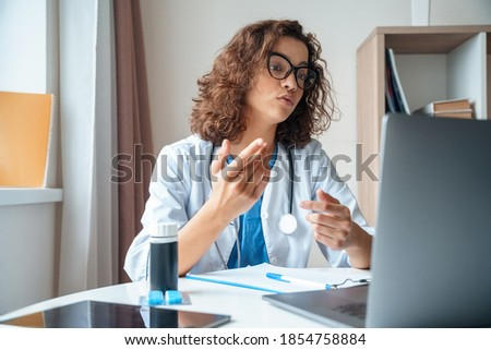 Attractive female doctor make online video call consult patient on laptop. Medical assistant young woman therapist videoconferencing to web camera. Telemedicine concept. Online doctor appointment.