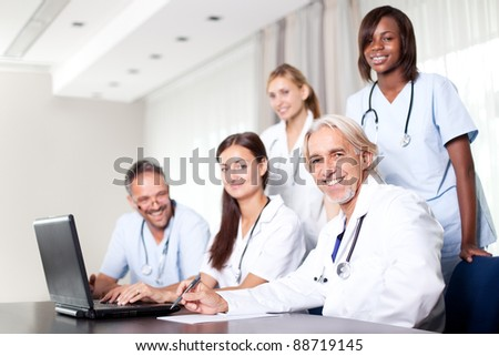 Attractive female doctor working on her laptop with healthcare colleagues in her office