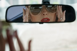 Attractive female driver in sun glasses looking in rear-view mirror in the car. Selective focus on the mirror