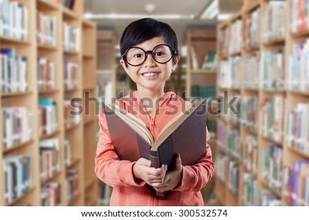 Attractive female elementary school student reading a literature in the library and smiling on the camera