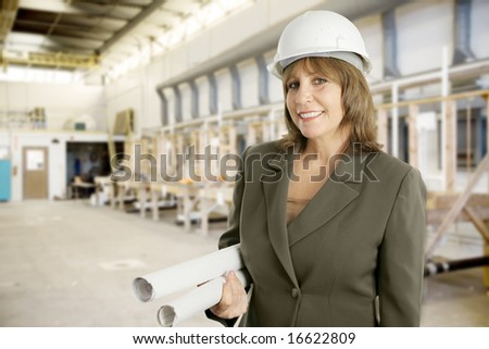 Attractive female engineer with blueprints on the floor of a factory.